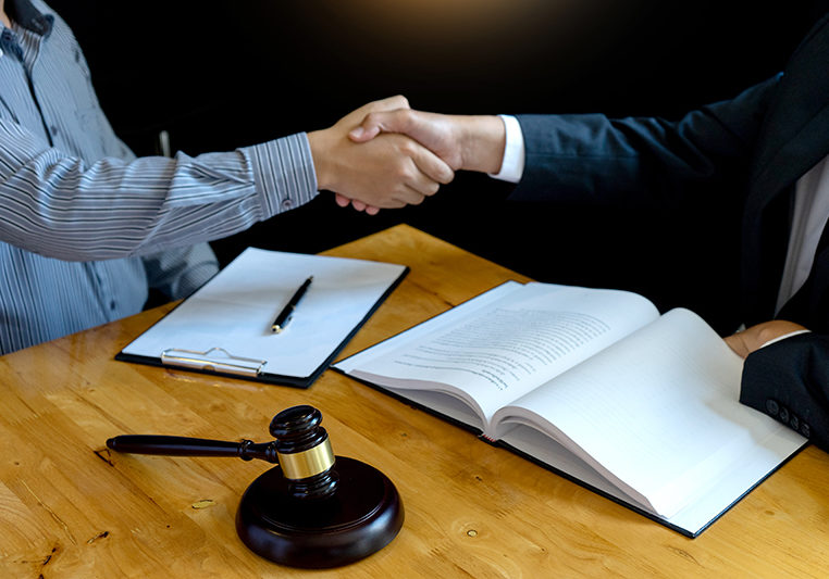 Two people shaking hands in a legal meeting